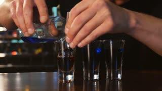 bartender preparing and lining shot glasses for alcoholic drinks on bar