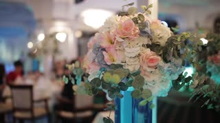 beautiful bouquet of flowers in a vase. The high glass vase on the table. festive table decoration