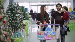 Beautiful family is shopping for Christmas at the supermarket. Mum takes son Christmas balls and boy smiling.