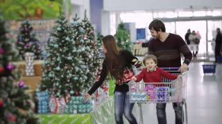 Beautiful family walking down the hall with a supermarket shopping carts and opt for Christmas toys and Christmas gifts. Little boy sitting in the shopping cart and consider buying.