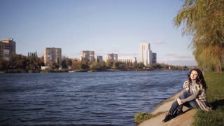 beautiful girl enjoys the view of the river. cold autumn wind develops your hair. soft sunlight reflected from water