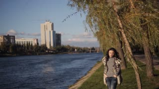 beautiful girl on the bank of the river. autumn wind develops your hair. soft sunlight