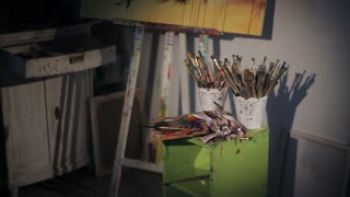 beautiful woman artist paints with oil painting. dirty workshop
