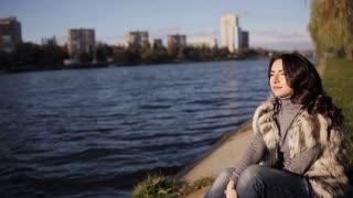 beautiful woman sitting at river bank