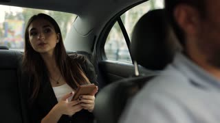 Beautiful woman tourist traveling in a taxi and rewritten with your friends on your phone