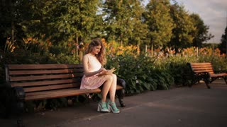 beautiful young blond woman sitting on a bench in the summer park and reading a book