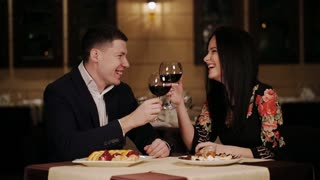 Beautiful young couple is drinking wine, talking and smiling at the restaurant
