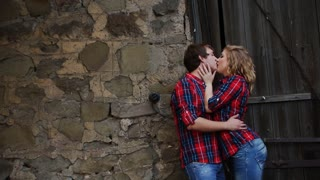 beautiful young couple standing near the door kissing