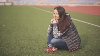 Beautiful young woman on the football field. Girl sitting on the green grass on the playground