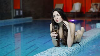 beautiful young woman swimsuit sitting with glass of champagne
