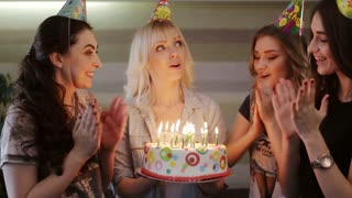 birthday girl makes a wish and blows out the candles on the cake