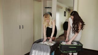 blonde and brunette stealing things into a suitcase