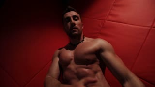 Brutal muscular man in the red room dancing. stripper handcuffed
