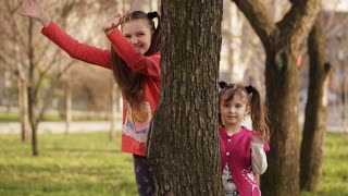 Cheerful girl playing hide and seek behind a tree