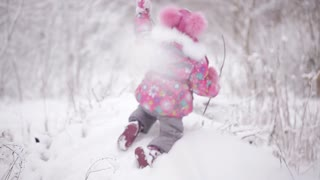 cheerful little girl playing in a winter forest with snow drifts