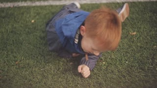 Cheerful red-haired boy is spinning on the green grass sport stadium