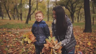 Cheerful red-haired little boy with his mother compre throw up yellow leaves in autumn park