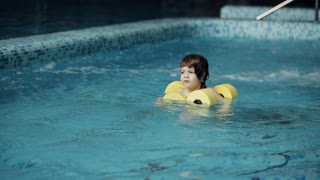 Child swims in the pool. Little boy swimming in the pool at the leisure center