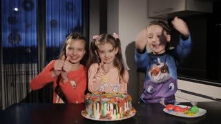 children show a thumbs up. children the right cake. funny little girl in the kitchen. birthday cake is on the table