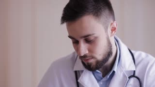 Close-up of a doctor, which makes palpation of the patient. Portrait of a doctor during the examination of the patient.