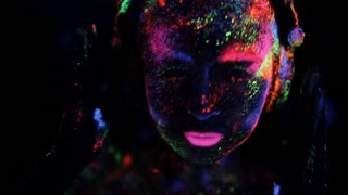 close-up of a girl wearing headphones colored fluorescent powder ultraviolet light