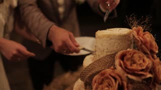 couple cut the wedding cake Rustic clouse-up. Outdoor