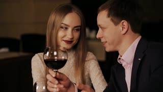 Couple in a restaurant drinking red vine