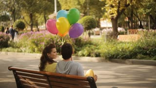 couple sitting on a bench in the park with balloons