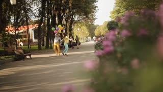 couple with balloons walking through the alleys of the park