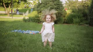 curly girl in a summer Park jumps