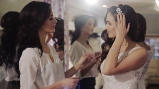 cute girl measures the wedding dress with the help of a consultant wedding salon