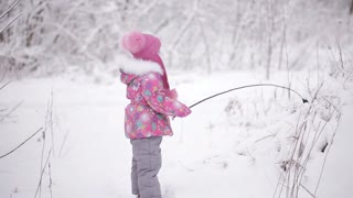 cute little girl playing in a winter forest with snow