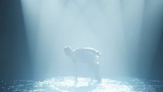 dancer does a break-dance in the water in a circle of light