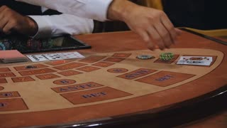 dealer moves the cards to player. The game of blackjack with an elegant woman