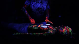 DJ controls, painted with a fluorescent powder on the body of a naked girl, decks