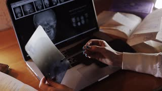 doctor looking at X-ray of the evening at a laptop