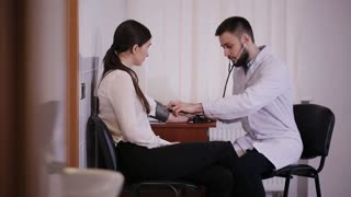Doctor's office. Male doctor measures the pressure of a patient girl.
