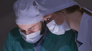 Doctors surgeons operate patient in operating theater, tilt down. Surgical team performing operation in hospital operating room. doctors making bloody cut with scalpel. Surgery on specialized clinic.