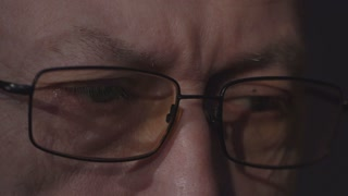 elderly man's eyes with glasses looking at a computer monitor