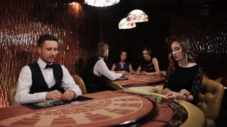 Elegant luxury girl in black dress playing blackjack in casino.