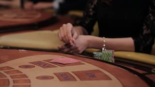 Elegant luxury girl in black dress playing in the casino. The girl makes a bet.