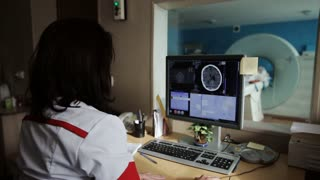 Experienced doctor looking at MRI scan of lumbar region on Monitor