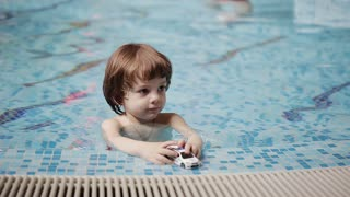 Family and son playing in the pool with toys