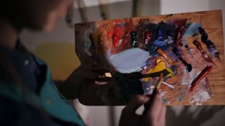 female artist mixes paint on the palette. close-up