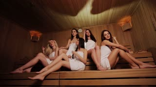 five sexy young women relaxing in a sauna
