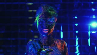 girl in ultraviolet light blows pink fluorescent powder with palm