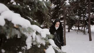 girl is in the winter woods and touches the snow on the branches of spruce