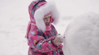 Girl sculpts a snowman in the snow in winter.