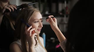 Girl Talking On The Phone While Make Up Artist Doing Professional Makeup  And Hair Stylist Makes