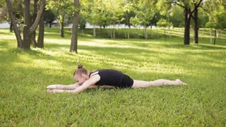 Girl teenager sitting in the splits on the grass and exercise.